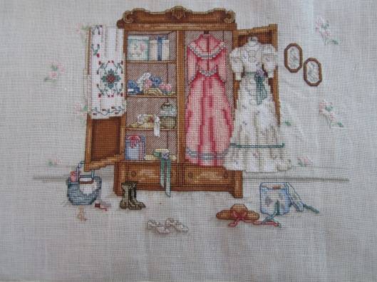 Cross stitch embroidery of antique wardrobe with dresses etc.